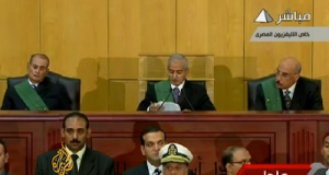 "Judge Ahmed Refaat (center) reads the verdicts in Egypt's ""Trial of the Century."" Photo: youtube user AlJazeeraEnglish."