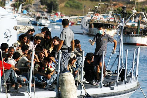 Migrants arriving at the island of Lampedusa by boat. Image via Wikipedia.