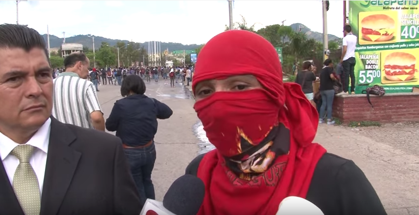UNAH student activists cover their faces to avoid arrest. Image via Youtube user: Canal 11 - Honduras.